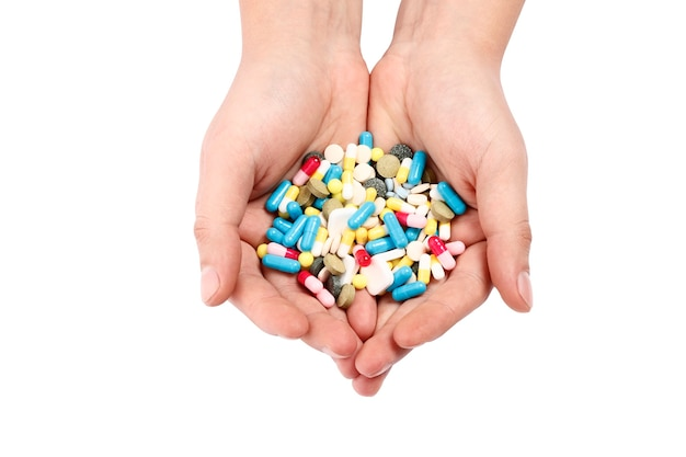 흰색 배경에 고립 된 손에 여러 가지 빛깔된 약입니다.