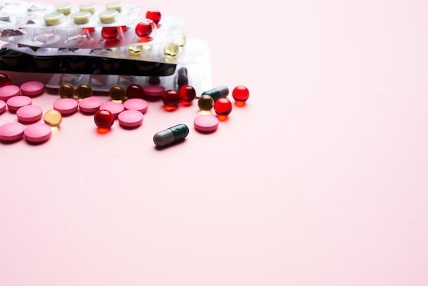 Разноцветные таблетки лекарство обезболивающее на розовом фоне