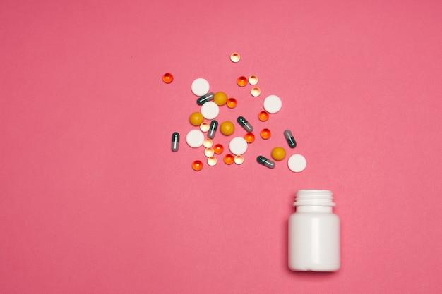 Разноцветные таблетки фармацевтические витамины розовый фон медицина