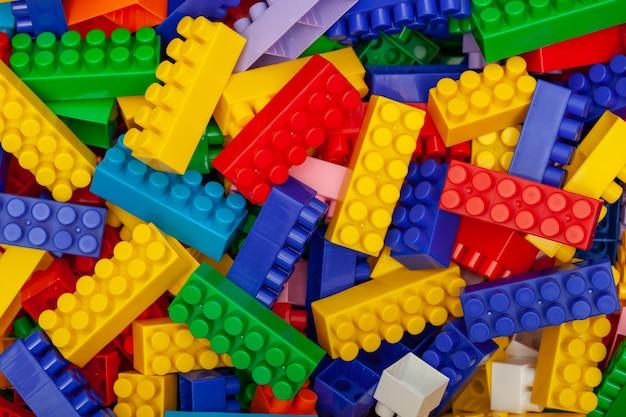 Разноцветные пластиковые строительные блоки конструктора. фон из ярких пластиковых строительных блоков.