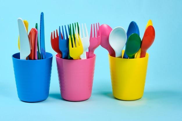 青い空間に色とりどりのプラスチック皿。プラスチックによる環境汚染の概念、テキスト、フラットレイアウトのエコログ場所