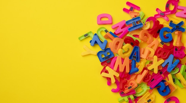 Multicolored plastic english alphabet letters with magnet on yellow surface