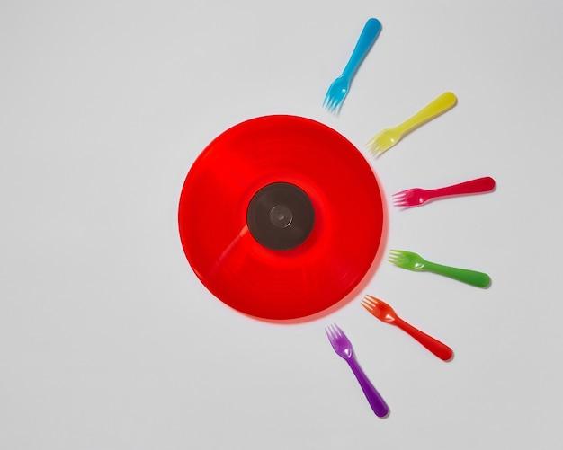 Разноцветные пластиковые вилки и красная виниловая пластинка в стиле ретро