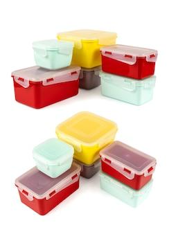 Разноцветные пластиковые ланч-боксы, сложенные в углу, изолированные на белом виде сбоку и сверху