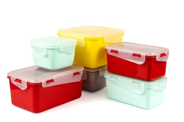 Разноцветные пластиковые ланч-боксы, сложенные в углу на белом фоне, вид сбоку