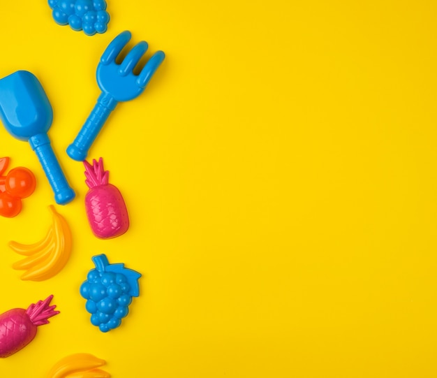 Multicolored plastic toys fruits on yellow
