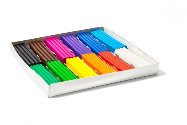 白い表面にある箱の中の多色の粘土。子供たちの明るい粘土。 Premium写真