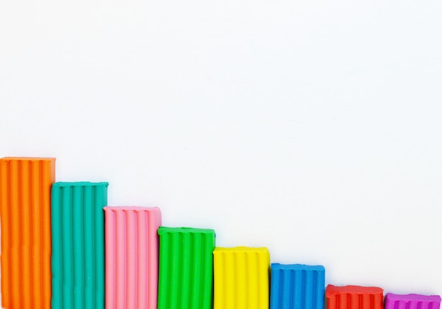 Multicolored plasticine located on a white background. kids toys background. frame with place for text.