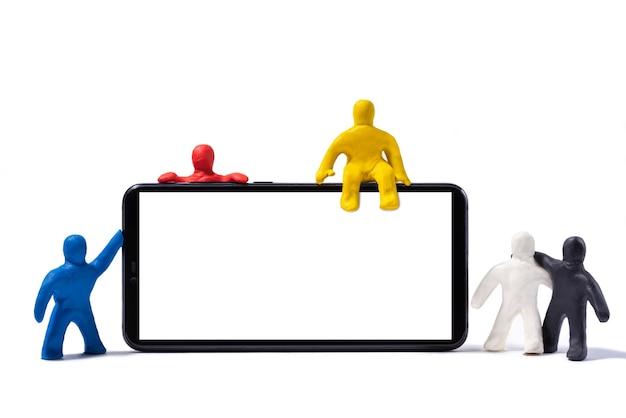 Разноцветные пластилиновые люди стоят у смартфона на белом фоне
