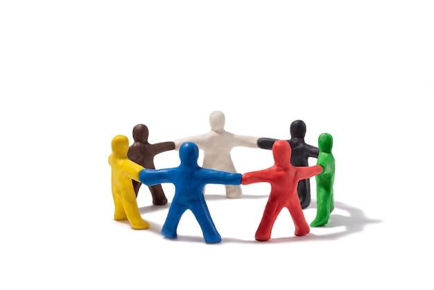 Разноцветные пластилиновые люди, стоящие в кругу, изолированном на белом концепция сообщества