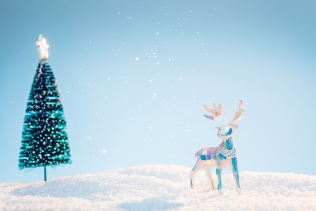 Multicolored polygonal christmas deer in the snow on a light blue sky background. background image with copy space