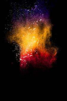 Взрыв разноцветного порошка на черном фоне