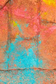 Multicolored powder from holi festival on red brick sidewalk