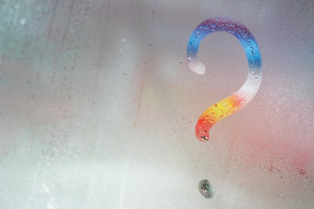Multicolored question mark on the window glass