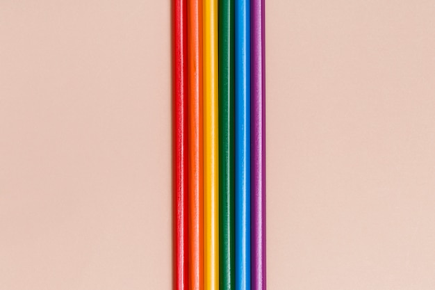 Multicolored rainbow sticks on beige background