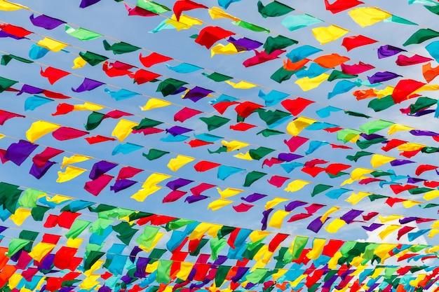 春のホーリー祭のための街の通りの青空のお祭りの装飾に対して色とりどりのリボン...