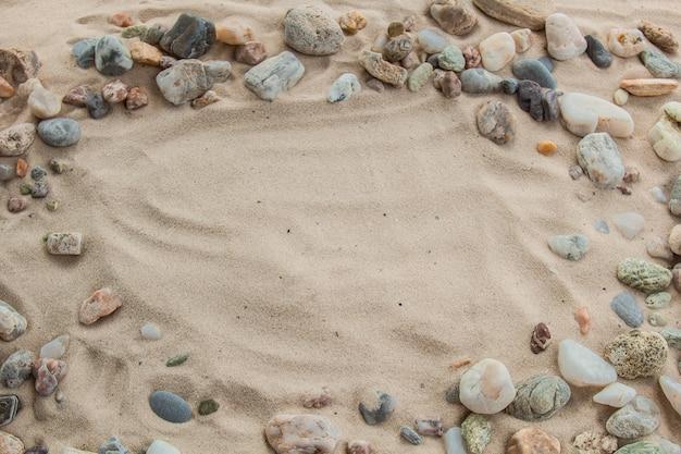 Разноцветная речная галька, камни случайно лежат на песке рядом с морем