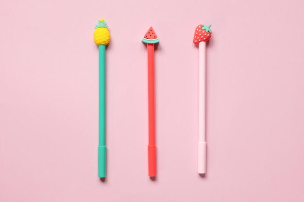 Multicolored school pens on pink background funny colorful back to school concept