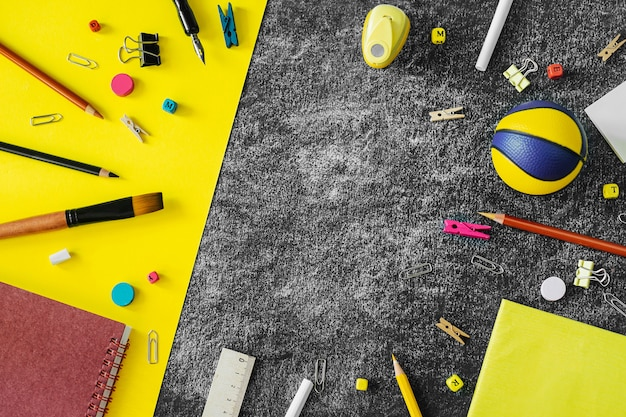 Multicolored school supplies on black and yellow blackboard background.