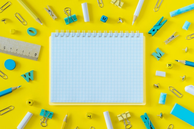 Multicolored school supplies and blank notebook background