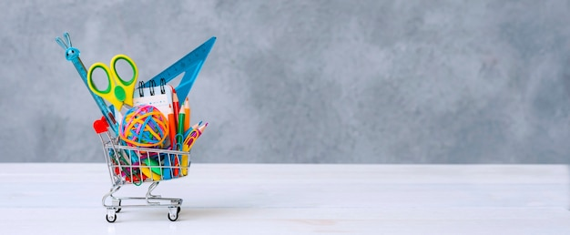 Multicolored school supplies in a shopping cart on a gray background with copy space for text