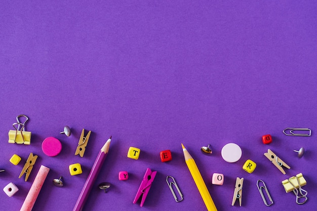 Multicolored school supplies on violet background with copy space.