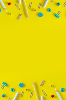 Multicolored school supplies on yellow background with copy space. vertical flat lay for social media stories