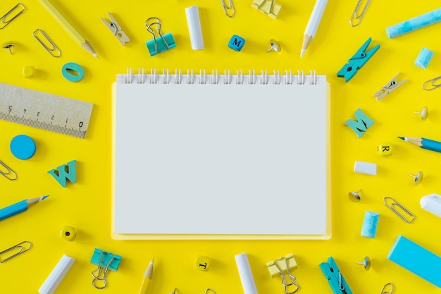 Multicolored school supplies on yellow background with copy space