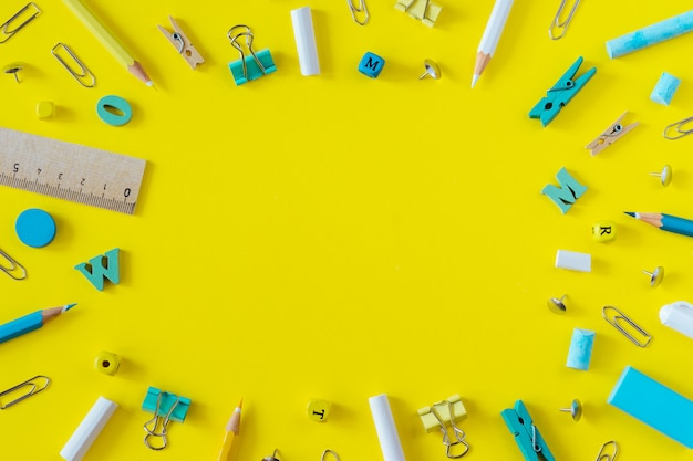 Multicolored school supplies on yellow background with copy space.