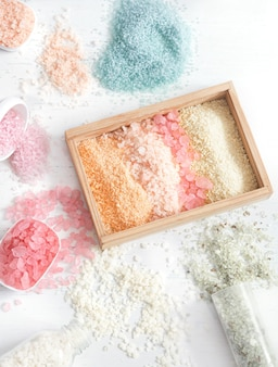 Multicolored sea salt and bath set on light background top view, flat lay.