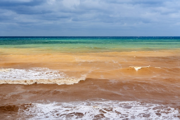 空と水の間の曇りの天気の地平線の色とりどりの海の風景