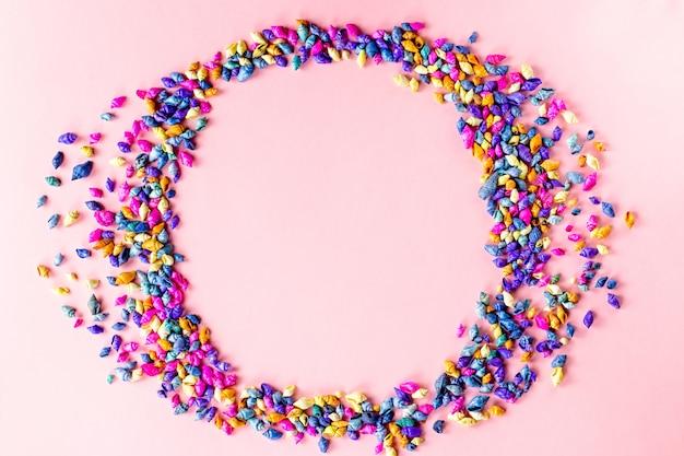 Разноцветные ракушки кадр фон на розовом