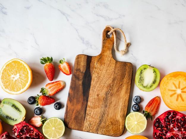Разноцветные сезонные здоровые натуральные фруктовые бордюры с хурмой, черникой, апельсином, киви, клубникой, грейпфрутом, гранатом, дольками апельсина.