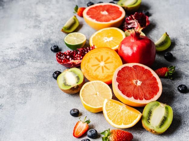 Разноцветная сезонная полезная натуральная фруктовая композиция с хурмой, черникой, апельсином, киви, клубникой, грейпфрутом, гранатом, дольками апельсина. копировать пространство