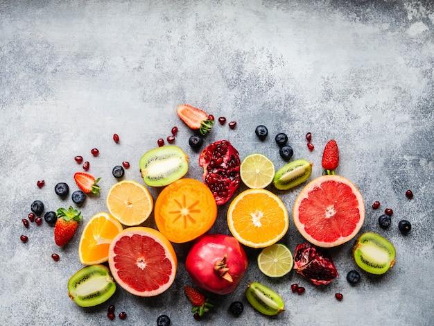 Разноцветная сезонная полезная натуральная фруктовая композиция с хурмой, черникой, апельсином, киви, клубникой, грейпфрутом, гранатом, дольками апельсина. вид сверху