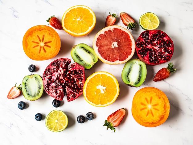 Разноцветная сезонная полезная натуральная фруктовая композиция с хурмой, черникой, апельсином, киви, клубникой, грейпфрутом, гранатом, дольками апельсина.