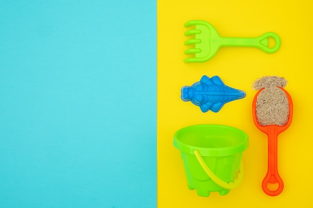 Multicolored set children's toys for summer games in sandbox or on sandy beach. background copyspace