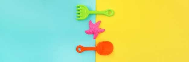 Multicolored set children's toys for summer games in sandbox or on sandy beach on blue yellow background.