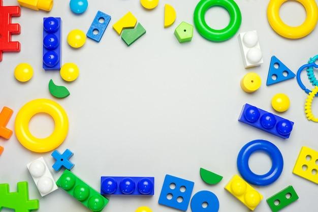 Multicolored set of developmental toys for children on gray