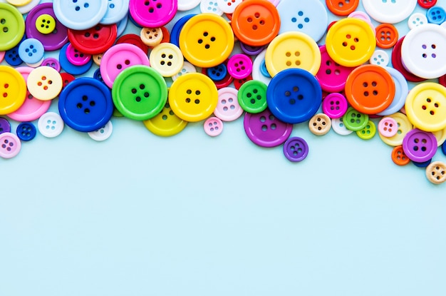Multicolored sewing buttons on a blue pastel surface. sewing border, top view