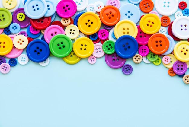 青いパステルカラーの背景に色とりどりの縫製ボタン。ソーイングボーダー、上面図