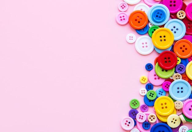 ピンクのパステルカラーの背景に色とりどりの縫製ボタン。ソーイングボーダー、上面図