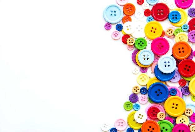 Разноцветные пуговицы на белой пастельной поверхности. швейный бордюр, вид сверху
