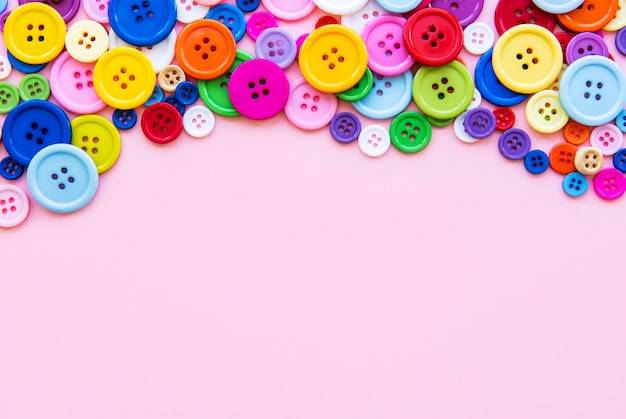 Multicolored sewing buttons on a pink pastel surface. sewing border, top view