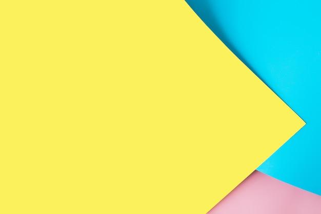 Разноцветные листы бумаги размещены геометрически и беспорядочно. разноцветная бумага желтого, розового, синего цветов