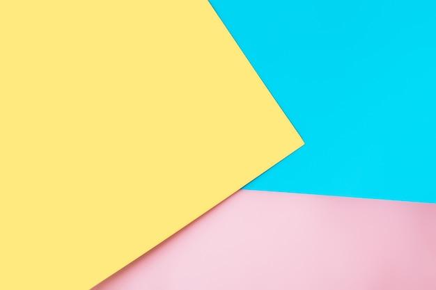 Разноцветные листы бумаги размещены геометрически и беспорядочно. желтый, розовый, синий цвета