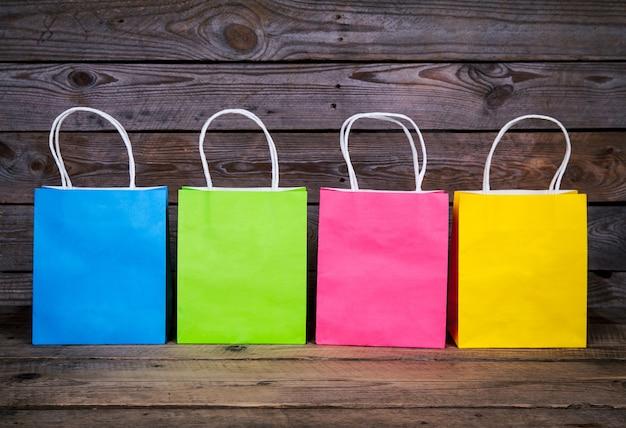 Разноцветные хозяйственные сумки на деревянном фоне, продажа