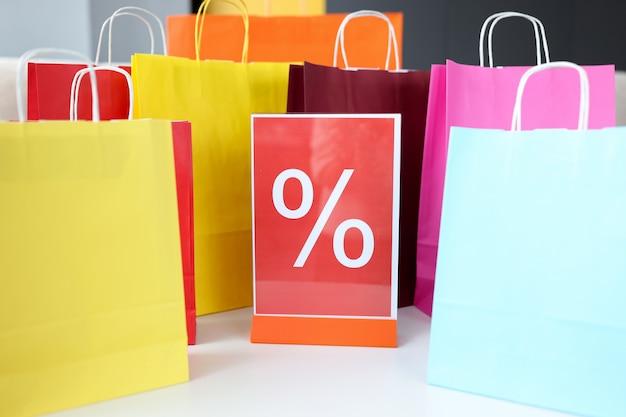 パーセント記号付きの色とりどりのショッピングバッグ。割引と販売コンセプト