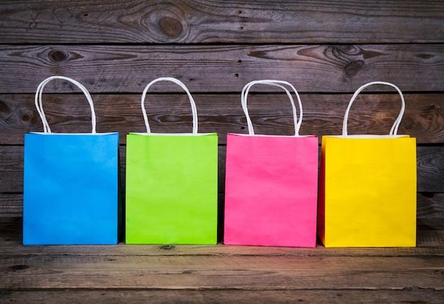 Multicolored shopping bags on a wooden background, sale