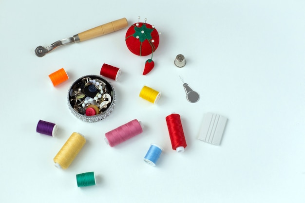 Multicolored skeins of thread, buttons, needles - sewing supplies